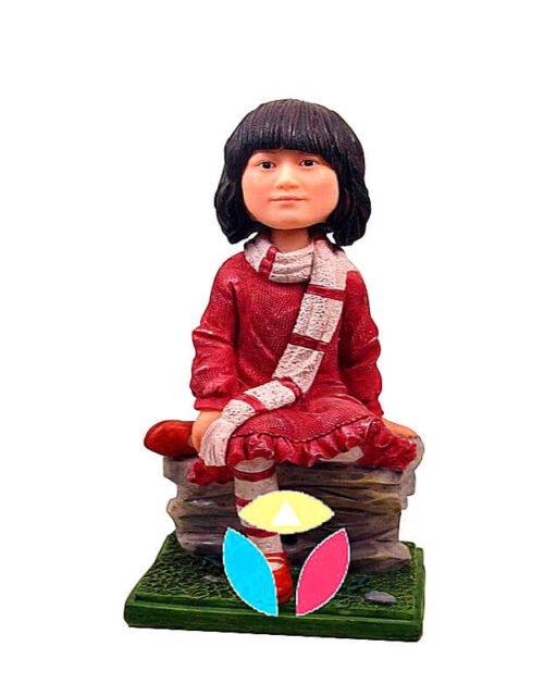 Teen girl sitting on the rock bobblehead doll